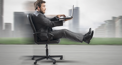 Businessman in office chair racing down a racetrack business growth