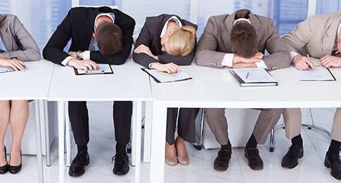 Group of tired corporate personnel officers sleeping at table in office because they didn't follow their security risk assessment.