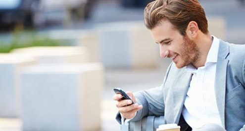 Happy businessman looking at mobile phone seated on park bench